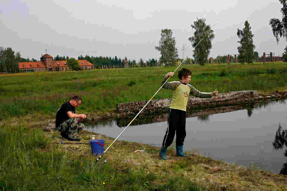 A father and son from the town of Brzezinka go fishing in flooded ruins of barracks at Auschwitz II-Birkenau.
