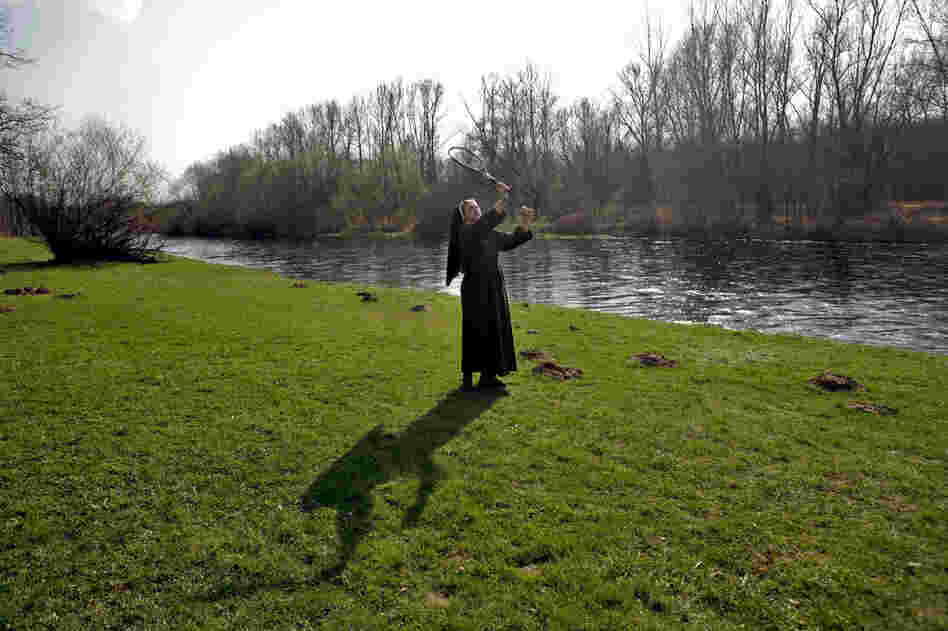 A nun plays badminton with school children on the banks of the Sola river in Oswiecim. About a mile down the river lies the concentration camp Auschwitz.