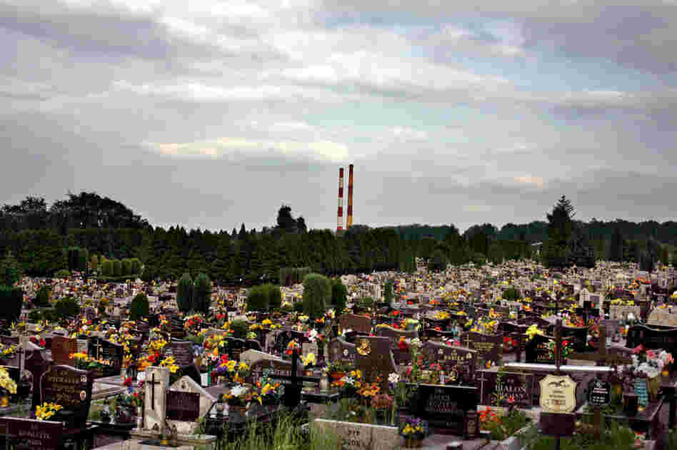A modern cemetery in the town of Oswiecim, with smokestacks from the town's chemical factory looming in the distance. The factory was built by Nazi Germany during the war and used prisoners from Auschwitz to run it.