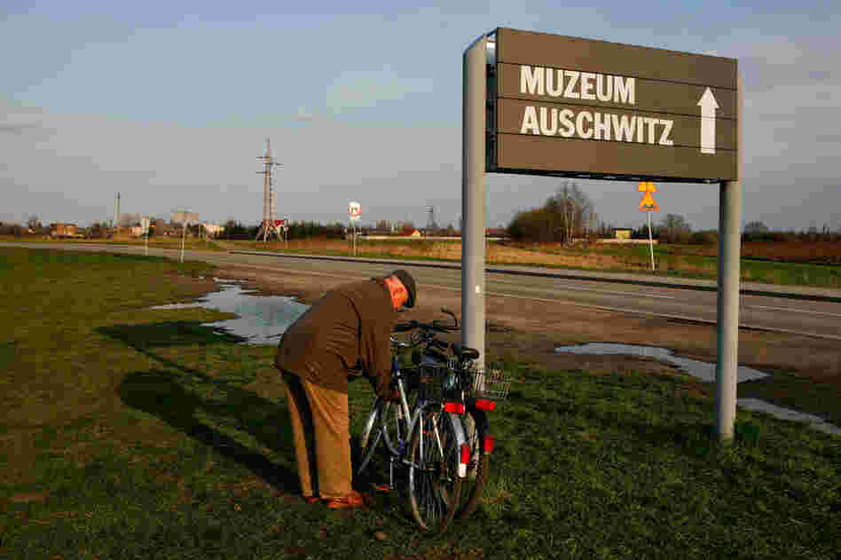 An elderly man from Oswiecim locks his bike to a sign at Auschwitz II-Birkenau that directs visitors to the Auschwitz museum site.