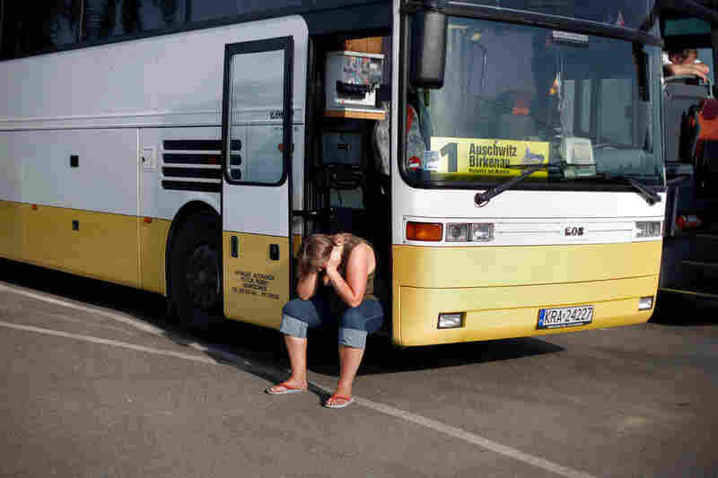 A tourist at Auschwitz II-Birkenau sits at a tour bus in the parking lot by the entrance.