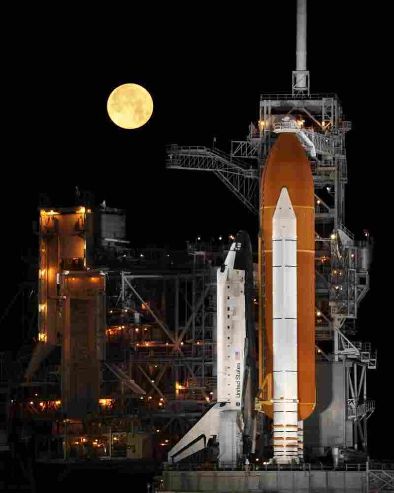 A nearly full moon sets as the space shuttle Discovery sits atop Launch Pad 39A at the Kennedy Space Center in Cape Canaveral, Fla., in the early morning hours of March 11, 2009.