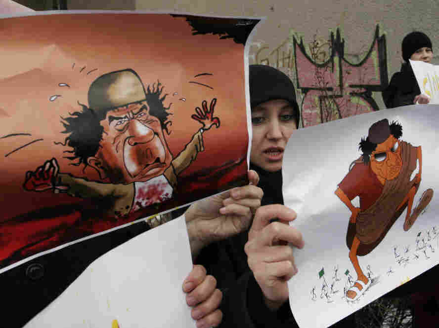 Demonstrators hold depictions of Libyan leader Moammar Gadhafi during a protest against the Libyan regime's crackdown on protestors, in front of the Libyan Embassy in Sarajevo, Bosnia, Wednesday.