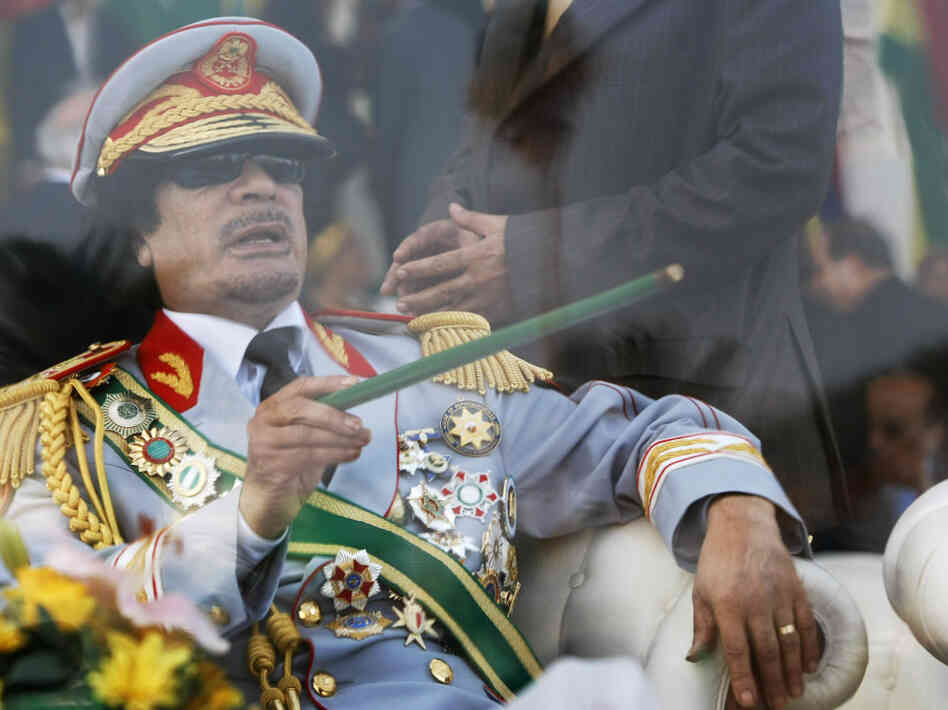 Sept. 1, 2009: Libyan leader Moammar Gadhafi gestures with a green cane as he takes his seat behind bulletproof glass for a militar