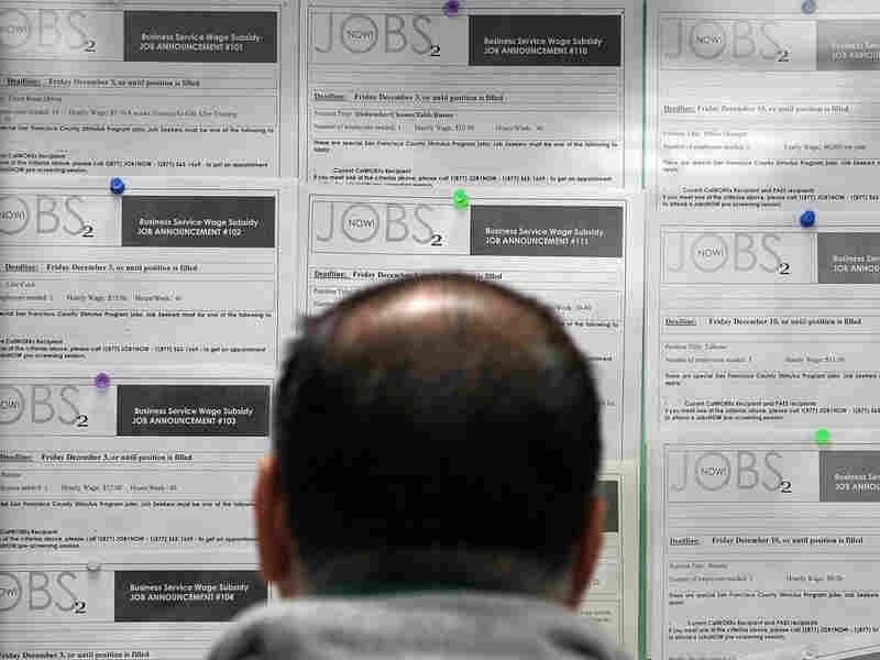 A job seeker looks at listings on a bulletin board.