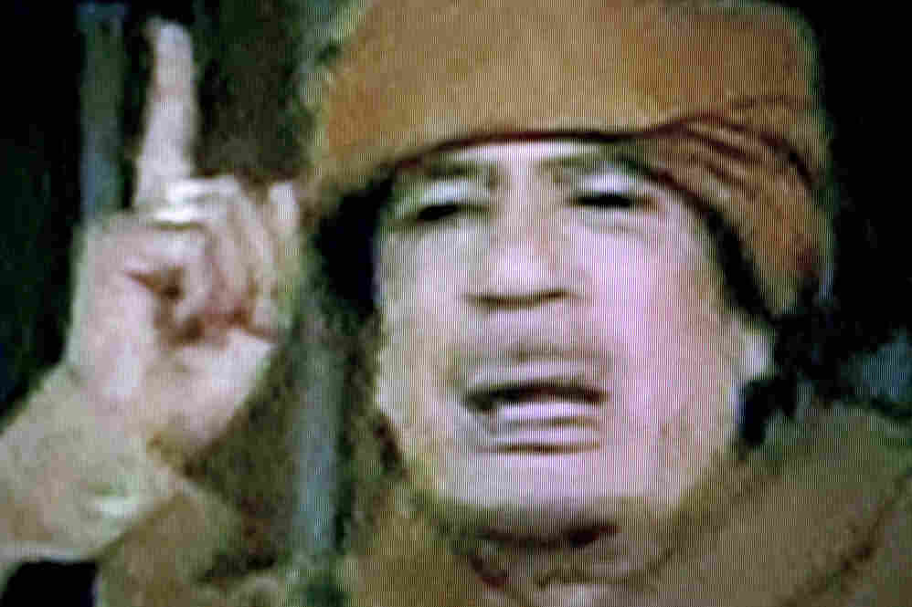 """A picture of a screen taken from the television on Tuesday shows Libyan leader Moamer Kadhafi gesturing while delivering a nationwide address in Tripoli. Kadhafi said he will stay in Libya, and vowed to fight to """"his last drop of blood."""""""