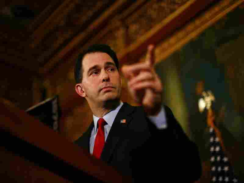 Republican Gov. Scott Walker speaks at a  news conference inside the Wisconsin State Capitol in Madison on Feb. 21 while people protest the legislation proposed by Walker to restrict collective bargaining.