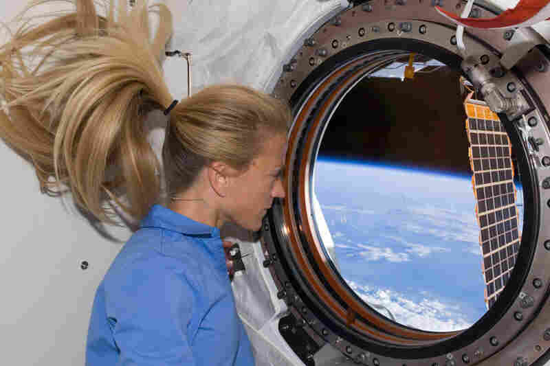 Astronaut Karen Nyberg peers through a window of the International Space Station's newly installed Kibo laboratory.  Space shuttle Discovery ferried the lab from Earth and  is docked with the space station.