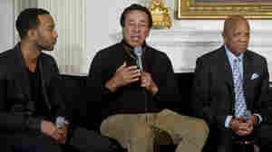 Smokey Robinson addresses the crowd at Thursday's White House musical event, flanked by singer John Legend (left) and Motown founder Berry Gordy.