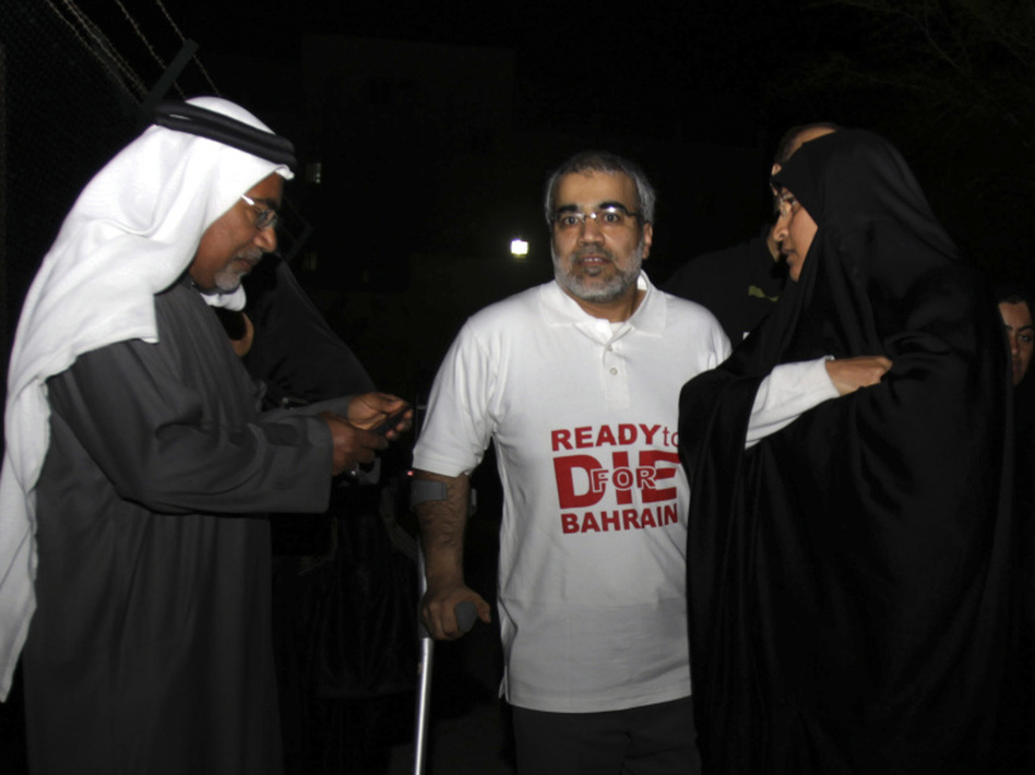 Abduljalil al-Singace (center), a Bahraini Shiite political activist who was released Wednesday, stands with his wife and other relatives outside the main police station in Manama, Bahrain.