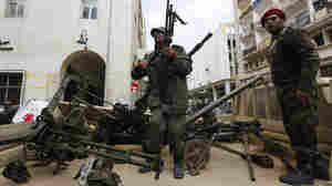 Gunmen prepared to fight against Libyan leader Moammar Gadhafi stand on a small military truck with weapons taken from a Libyan military base in Benghazi on Thursday.