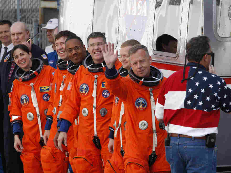 Commander Steve Lindsey, right, waves as he and the crew of space shuttle Discovery prepare to board the shuttle at pad 39A Thursday.
