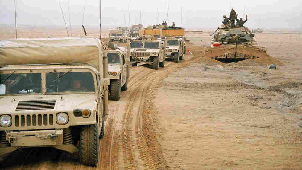 A U.S. Marines 2nd Division convoy moves past a tank equipped with a mine-clearing sled in Kuwait as the ground war gets under way Feb. 24, 1991.