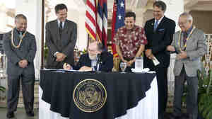 Hawaii lawmakers look on as   Hawaii Gov. Neil Abercrombie signs the Hawaii Civil Unions bill into law.