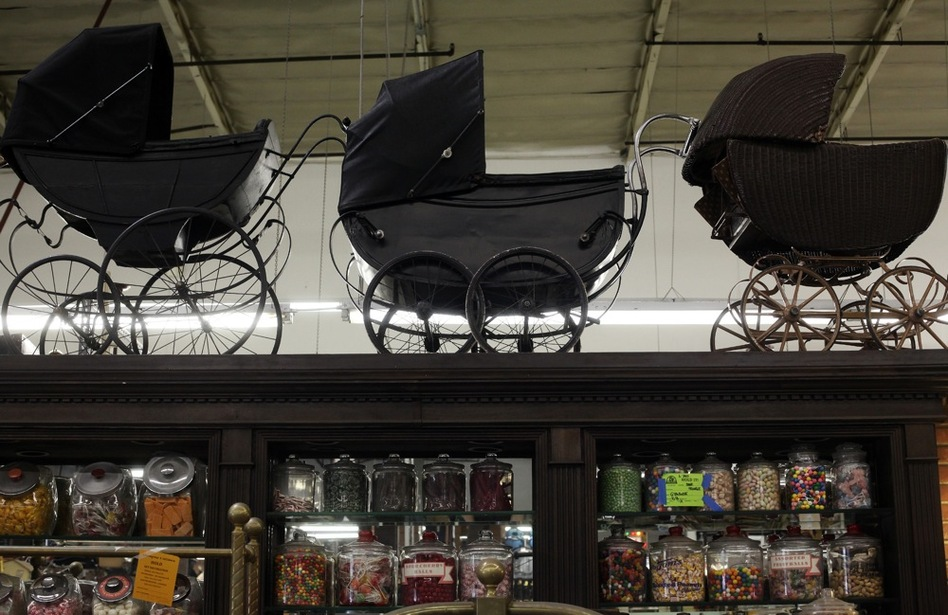 Buggies sit on top of a candy-store display. The center buggy is a pre-World War II English pram used in a movie about the Italian-American gangster Frank Nitty, as well as in one of the Addams Family films. To keep stagehands from snacking, the (real) candy in the jars is sprayed with water to fuse it together. (Katie Falkenberg for NPR)