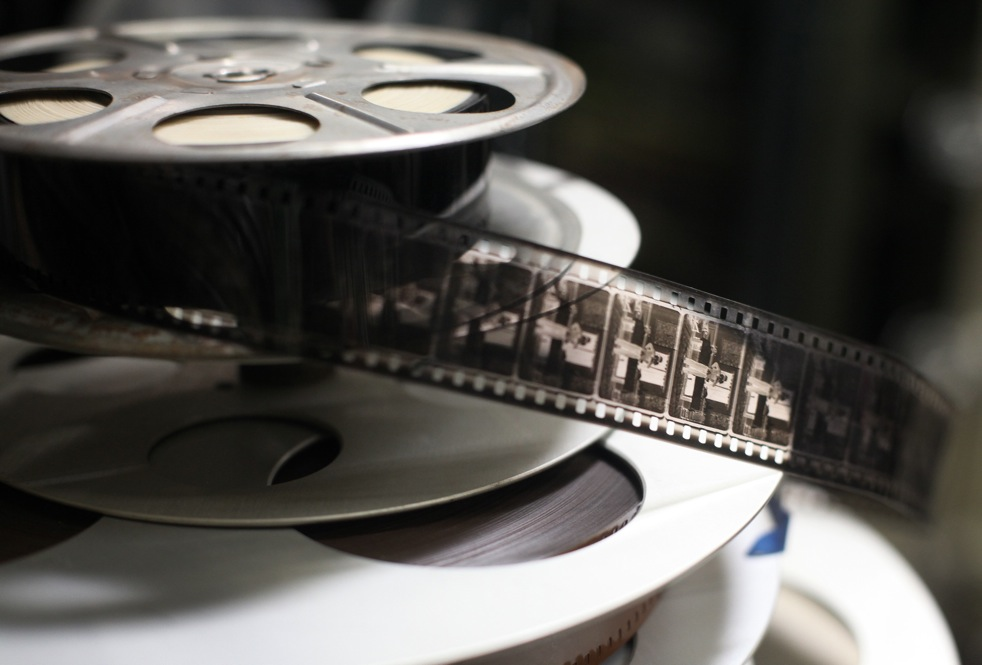 This '40s-era film reel contains early unknown black-and-white footage, likely from the silent movie era. The reels beneath it are later split reels, likely the ones used in Good Night and Good Luck.