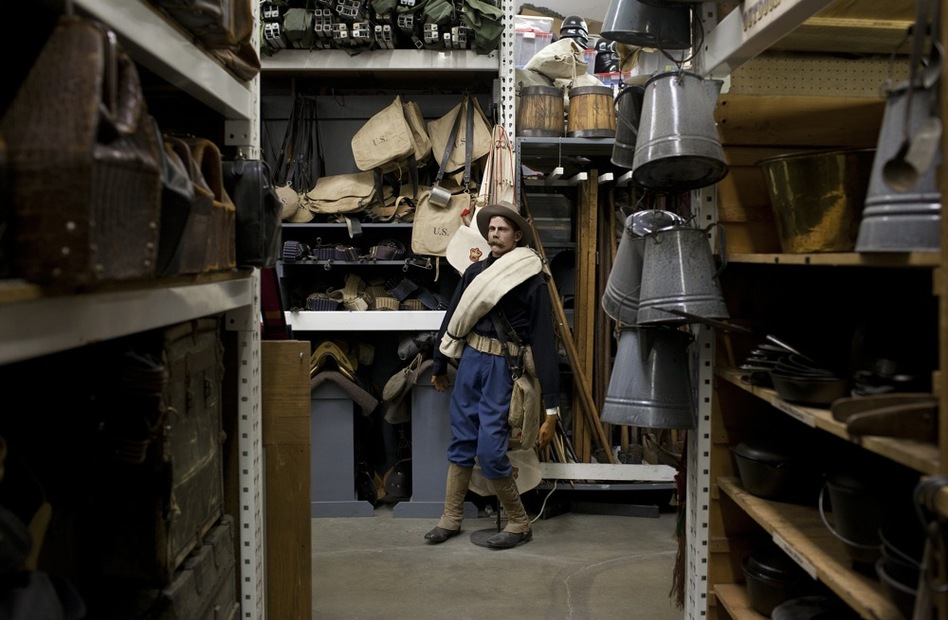A mannequin dressed in Spanish-American war gear stands at the end of one of the aisles in the military-outfitting section of History for Hire.  While the prop house doesn't carry uniforms, it does carry plenty of the equipment and leather gear.  The coffee pots in the foreground were used in  Tombstone and Wyatt Earp. (Katie Falkenberg for NPR)