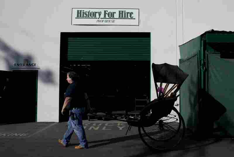 """Outside the warehouse, Elyea wheels a rickshaw used in several movies, including some filmed in Asia. """"We've shipped rickshaws to Japan, ski goggles to Norway and Pepsi bottles to Pepsi,"""" Elyea says. History for Hire props have been to all seven continents."""