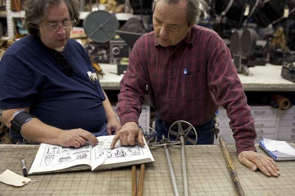 Jim Elyea (left) and shop manager Gary Aardahl look over examples of infantry equipment fielded by the major world powers in World War I and World War II. They are researching Spanish military equipment from 1936 to 1939 for an upcoming HBO show about Ernest Hemingway. (Katie Falkenberg for NPR)