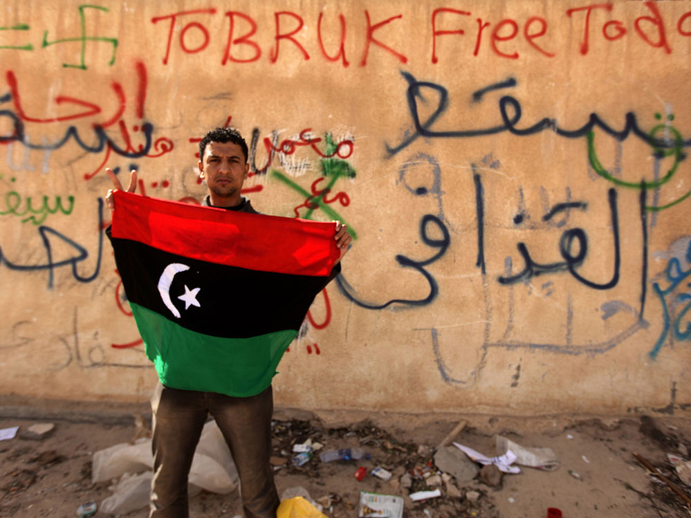 A protester holds an old national flag in front of a wall covered with graffiti against Libyan leader Moammar Gadhafi in the eastern city of Tobruk on Thursday.