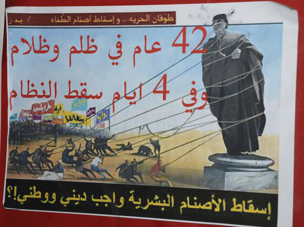 """An anti-Gadhafi placard in Benghazi reads """"A flood of freedom, topple the idols of oppression, 42 years of repression and darkness, in four days the regime fell, toppling the human idols is a religious and national duty""""."""