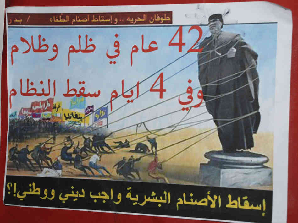 "An anti-Gadhafi placard in Benghazi reads ""A flood of freedom, topple the idols of oppression, 42 years of repression and darkness, in four days the regime fell, toppling the human idols is a religious and national duty""."
