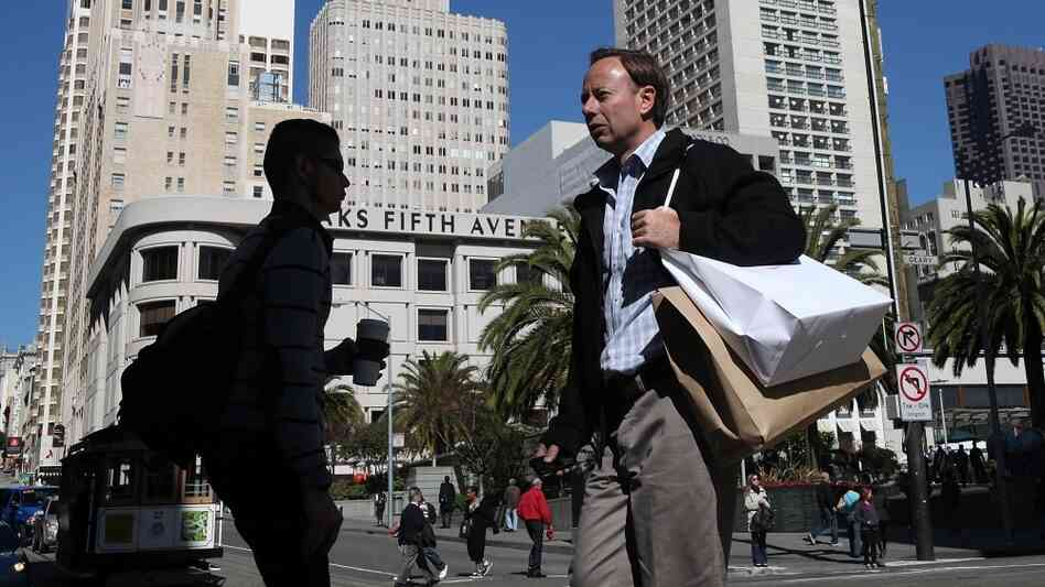 A pedestrian carries shopping bags as he walks through Union Square in San Francisco.  The Conference Board's Consumer Confidence Index reached the highest level in three years in February.