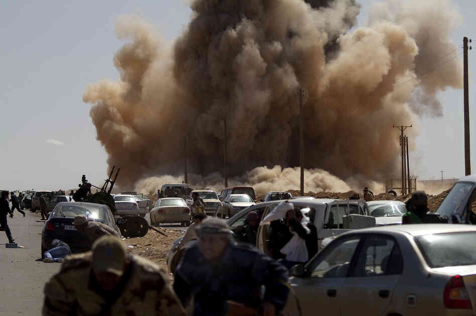 Rebel fighters take cover as a bomb dropped by an air force fighter jet explodes near a checkpoint