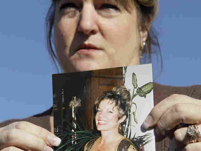 Nina Crossland holds up a photo of her aunt Phyllis Macay. The U.S. military says pirates killed Macay and three other American hostages they were holding on a yacht off Somalia's coast.