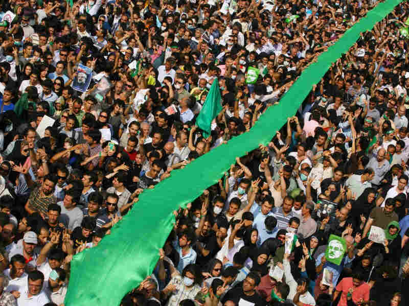 Iranians carry a large green flag through the crowd as they demonstrate in the streets on June 15, 2009 in Tehran, Iran to protest the re-election of Iran's President Mahmoud Ahmadinejad.