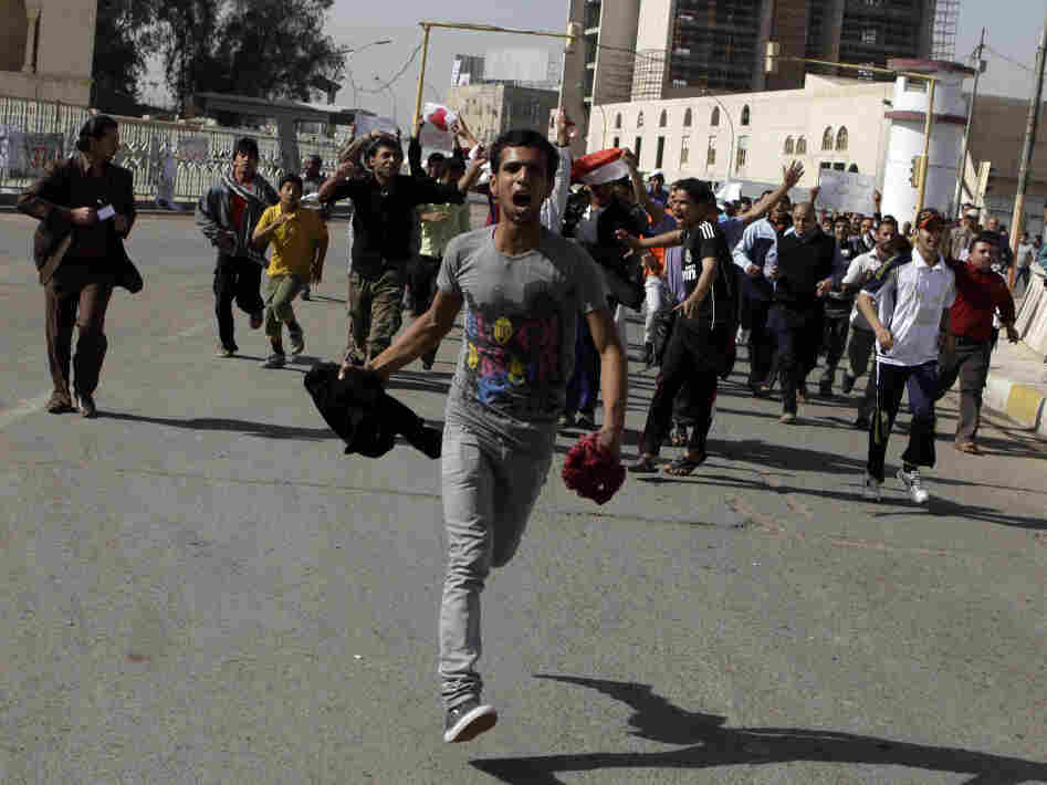 """Protesters run as they chant anti-Iraqi government slogans during a protest in Baghdad's Tahrir Square. Hundreds of demonstrators converged on central Baghdad as part of a rally inspired by uprisings across the Middle East and dubbed the """"Day of Rage."""""""