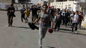 "Protesters run as they chant anti-Iraqi government slogans during a protest in Baghdad's Tahrir Square. Hundreds of demonstrators converged on central Baghdad as part of a rally inspired by uprisings across the Middle East and dubbed the ""Day of Rage."""