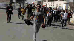 Protesters run as they chant anti-Iraqi government slogans during a protest in Baghdad's Tahrir Square. Hundreds of demonstrators converged on central Baghdad as part of a rally inspired by uprisings across