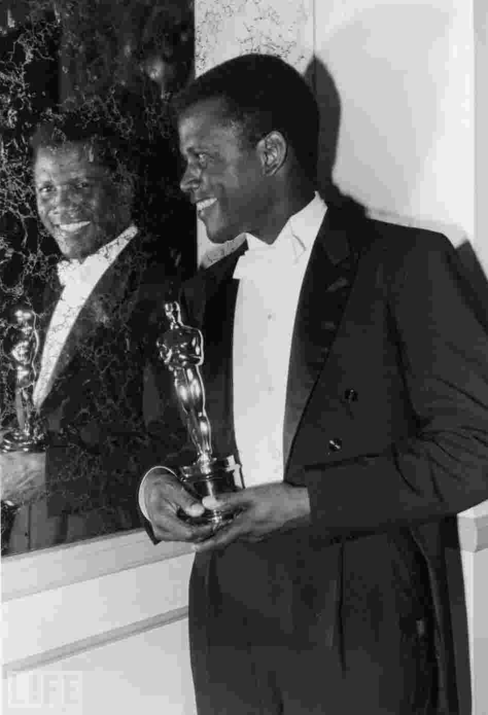 Sidney Poitier beams backstage after becoming the first black performer to win a  lead acting Oscar, for his handyman role in Lilies of the Field in 1964.