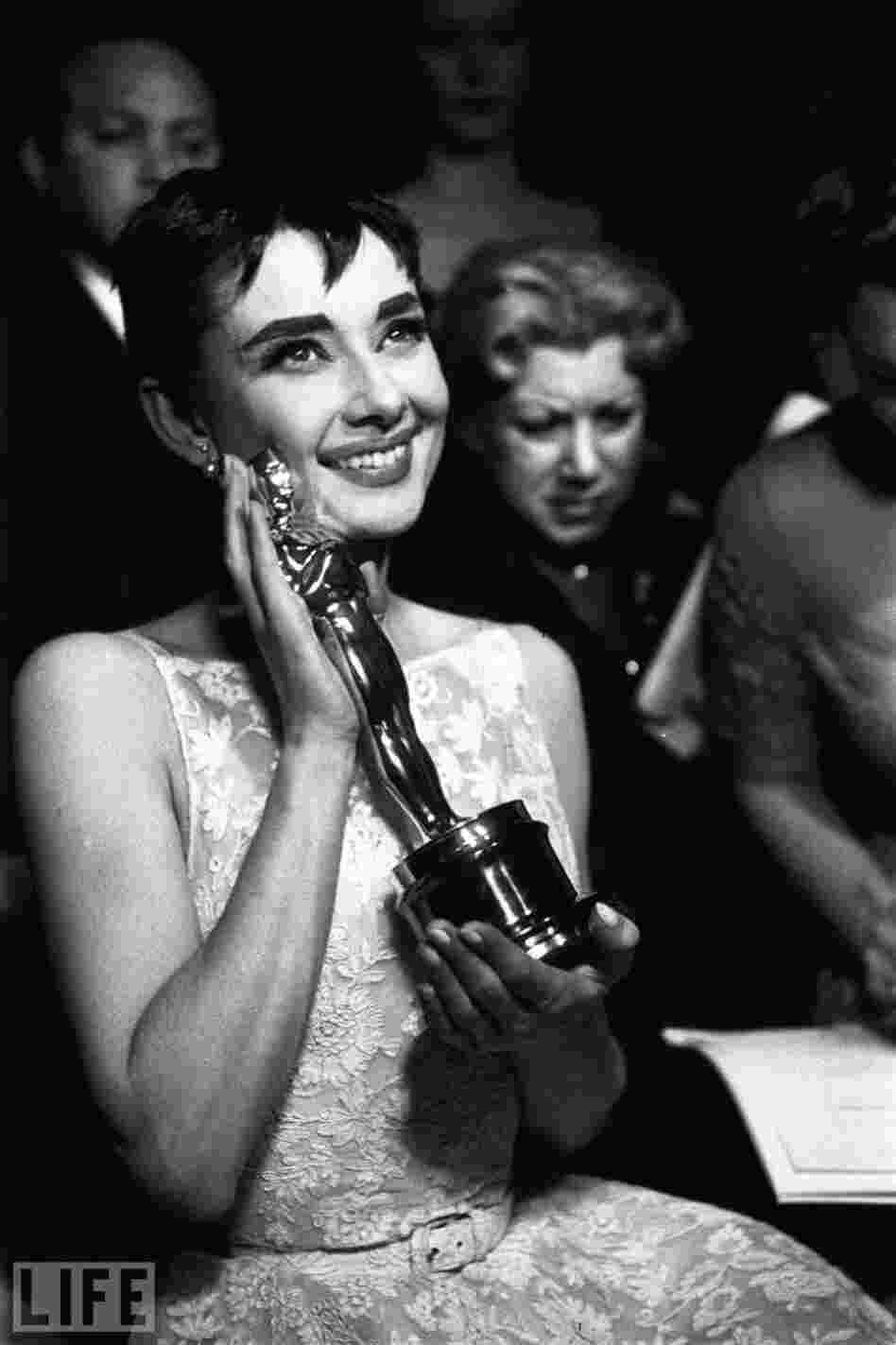 At the 1954 Academy Awards, Audrey Hepburn cradles the Oscar for best actress, awarded for her first lead role and her first Hollywood movie, Roman  Holiday.