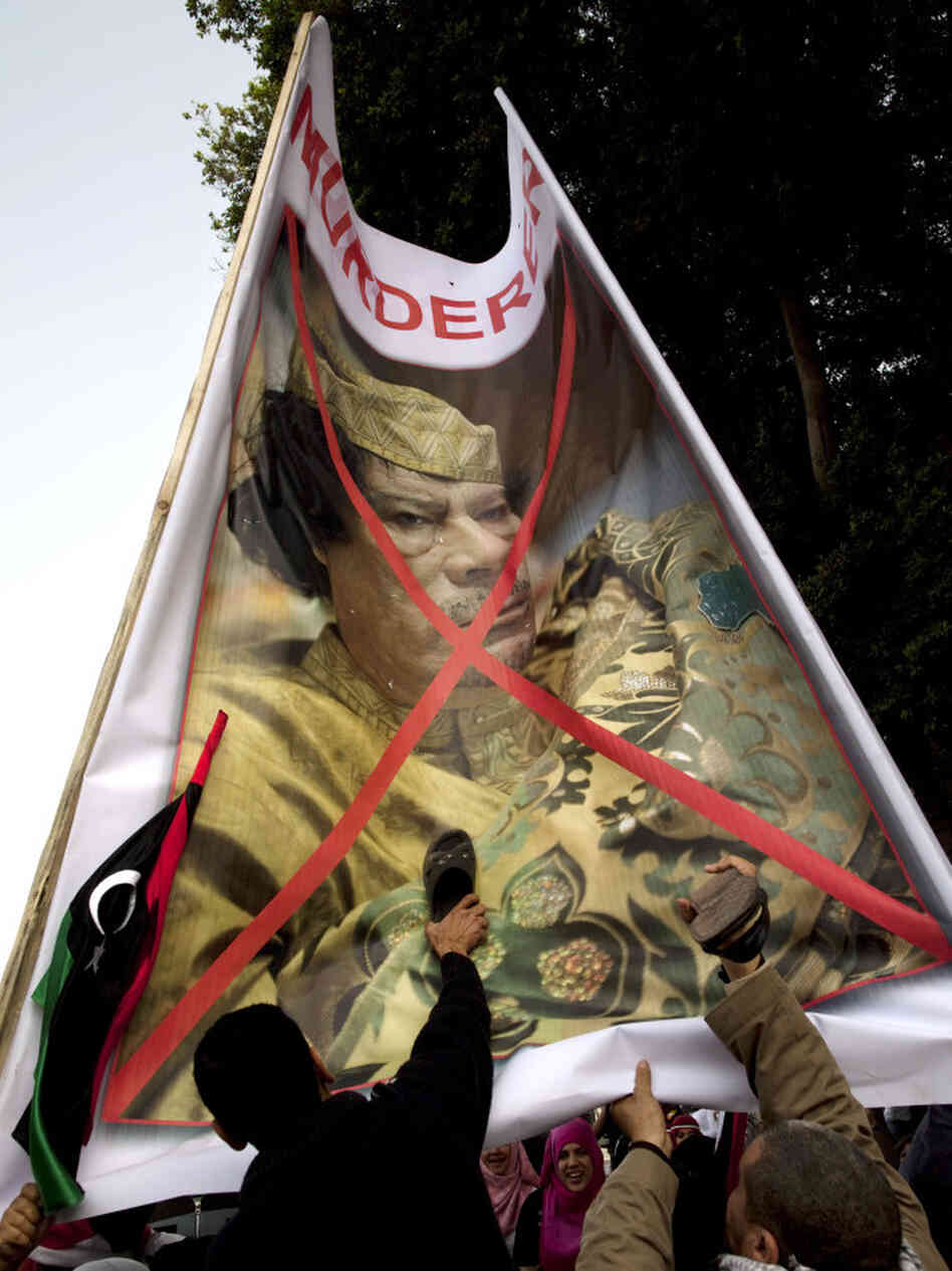 Egyptian protesters beat their shoes against a poster of  Libyan leader Moammar Gadhafi. They gathered Friday in Cairo's Tahrir Square to demand that he step down.