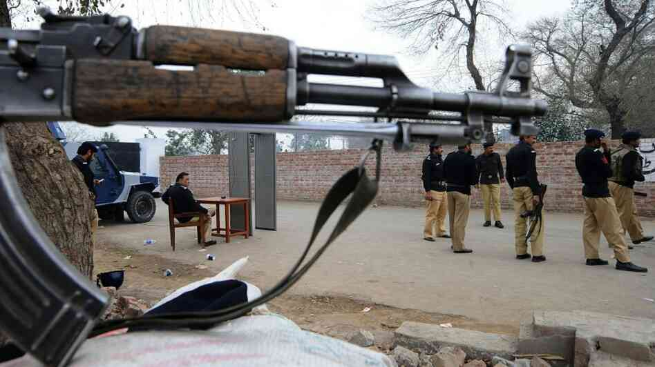 Pakistani police stand guard outside the Kot Lakhpat jail during today's court hearing.