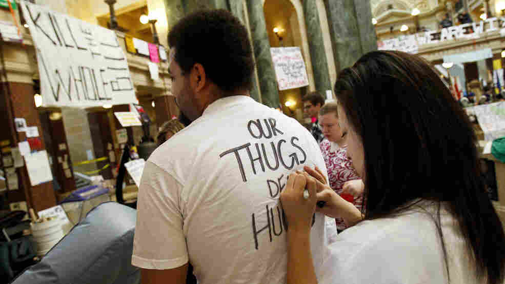 A protester writes on another's shirt on day 11 of protests at the Wisconsin state Capitol in Madison, Friday, Feb. 25, 2011.