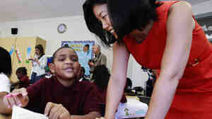 Rhee talks to a student at a school in Washington, D.C.