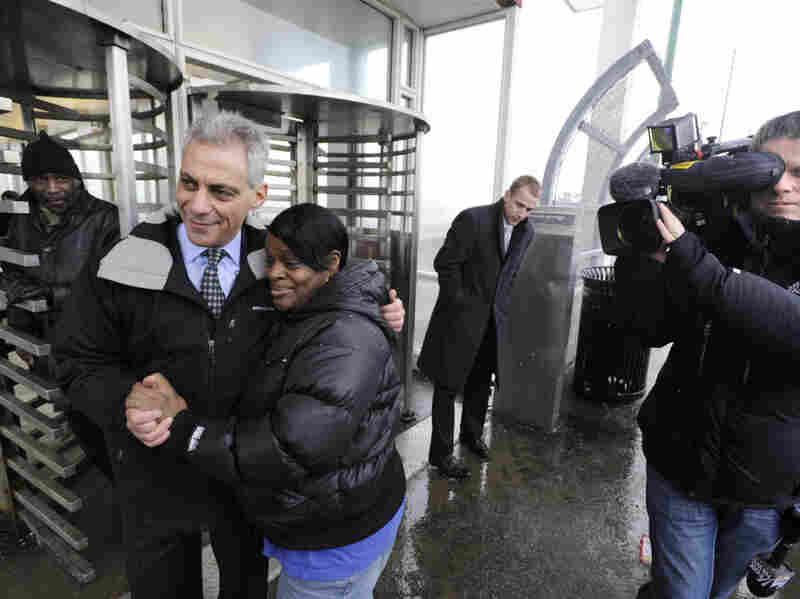 """Chicago mayoral candidate Rahm Emanuel poses with constituents at an """"L"""" station in Chicago Tuesday."""