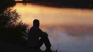 Man sitting by river. iStockphoto.com.
