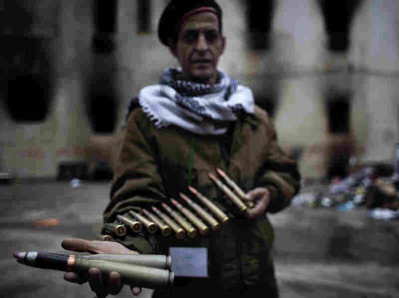 A Libyan rebel fighter displays heavy caliber ammunition found at a military barracks in Benghazi on Sunday.