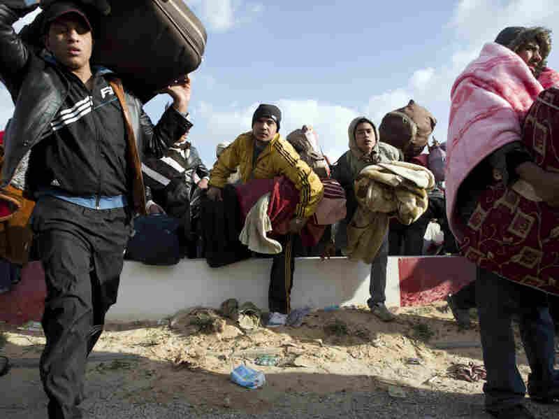 Egyptian people fleeing Libya race to get on buses at the Ras Jedir border post, near the Tunisian city of Ben Guerdane, on Sunday.