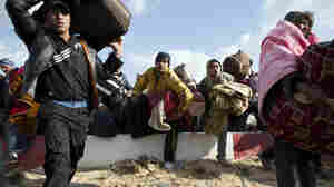 Egyptian people fleeing Libya race to get on buses at the Ras Jedir border post, near the Tunisian city of Ben Guerdane, on Sunday.