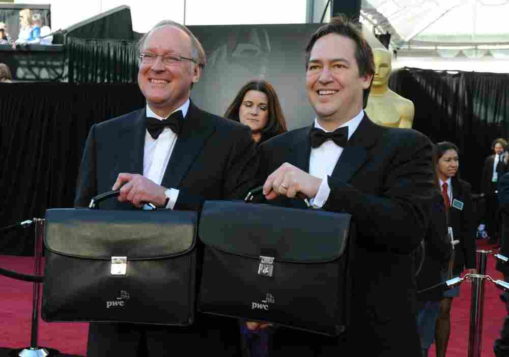 Rick Ross (L) and Brad Oltmann of Price Waterhouse Cooper arrive with briefcases containing the winners' envelopes.