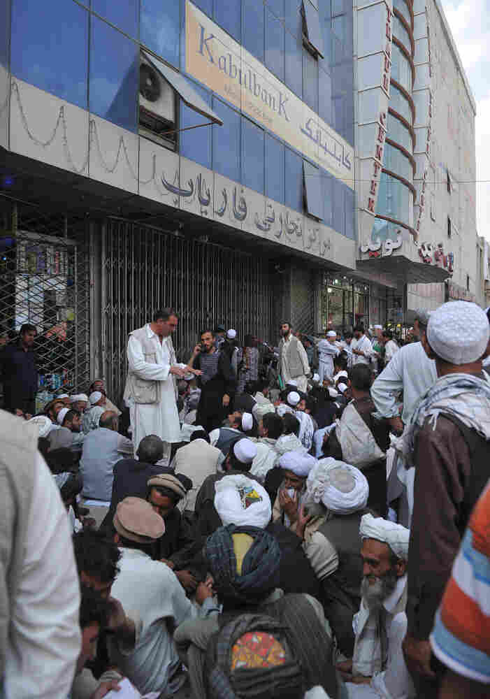 Men stand before the main branch of the Kabul Bank in Kabul on Sept. 5. Branches of the Afghan bank were crowded with government employees waiting to be paid and customers who wanted to withdraw their money following corruption allegations.