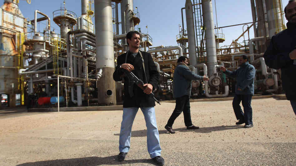 A militiaman stands guard at a Libyan oil refinery in the rebel-held territory of al-Brega on Feb. 27. The opposition leadership has stressed that oil facilities in areas under its control are safe, despite the conflict roiling the country.