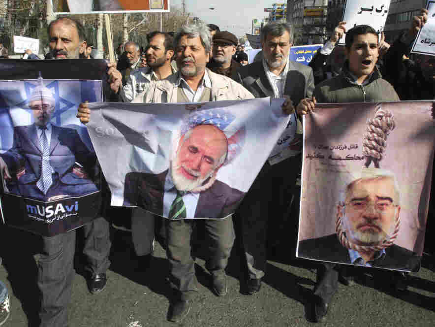 Pro-government Iranian demonstrators carry mocking photos of opposition leaders Mir Hossein Mousavi (left and right) and Mahdi Karroubi during a rally after Friday prayers in Tehran, Friday, Feb. 18.