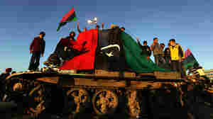 Anti-Gadhafi protesters wave their old national flag as they stand atop an abandoned army tank in the eastern Libyan city of Benghazi on Monday.