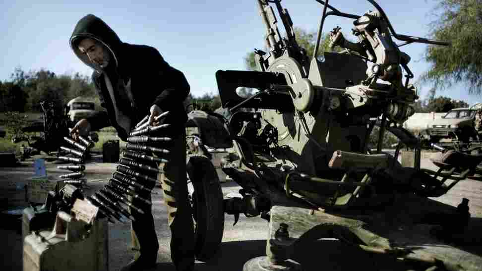 A Libyan civilian holds anti-aircraft ammunition at an army barracks in Benghazi, where dozens of civilians registered for civil defense  training amid fears of air raids from Tripoli.